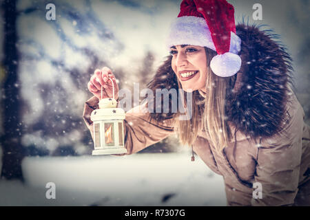 Christmas time - Young happy woman in Santa hat holding Christmas lantern outdoors on beautiful winter snow forest - Stock Photo