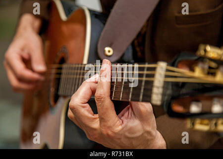 Close-up of the hands of a musician playing the guitar. The fingers of the musician are pressing the strings on the guitar. Musician playing bass guit - Stock Photo