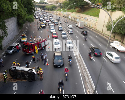 Extrication scene, firefighters and 'Traffic Engineering Company (CET)' at the car rollover accident scene, Av. 23 de Maio, Paraiso, Sao Paulo, Brazil - Stock Photo