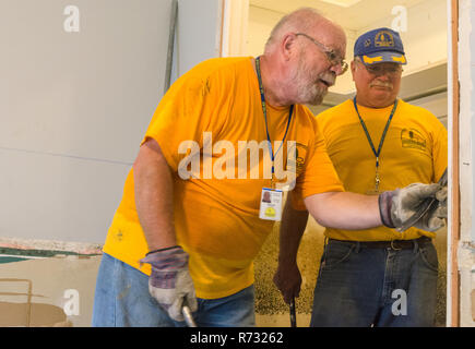 Southern Baptist Disaster Relief volunteers remove a damaged door frame from a flooded house after a flood in Baton Rouge, Louisiana. - Stock Photo