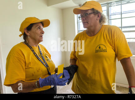 Southern Baptist Disaster Relief volunteers talk as they help clean out a flood victim's house after a flood in Denham Springs, Louisiana. - Stock Photo