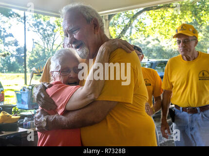A flood victim hugs a Southern Baptist Disaster Relief volunteer after a flood in Baton Rouge, Louisiana. - Stock Photo