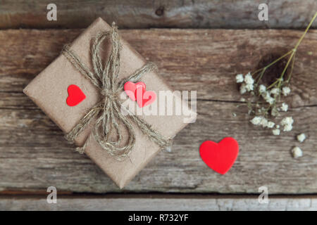 Gift box present wrapped craft paper with red hearts on rustic trendy old vintage wooden background. Christmas happy Holiday greeting card anniversary - Stock Photo