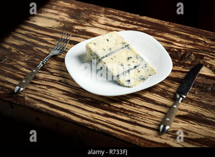 Aromatic and pungent. Piece of cheese on plate. Blue cheese food. Roquefort cheese. Gorgonzola cheese. Italian or danish cuisine on wooden table. Dairy food - Stock Photo
