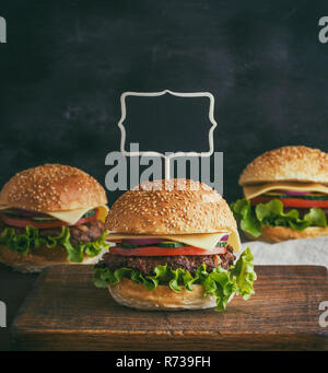 empty wooden pointer is stuck in a large hamburger - Stock Photo