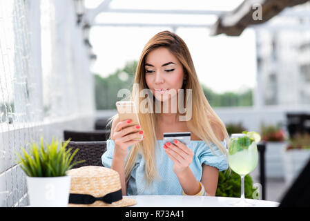 Beautiful girl with long hair in summer cafe in fresh air. Makes purchase through phone, a plastic card. Emotional happy smiling. The concept of online shopping. Pays lunch, breakfast in restaurant. - Stock Photo