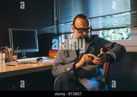 Man using cellphone at desk - Stock Photo