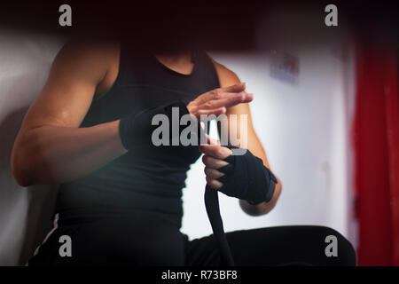 Female boxer putting on handwrap - Stock Photo