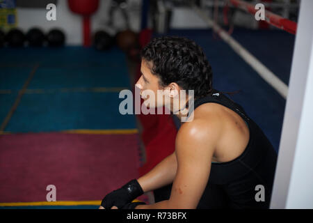 Female boxer resting in gym - Stock Photo