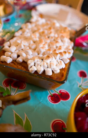 Macro shot of Thanksgiving homemade sweet potato casserole dish with marshmallows on retro tablecloth with cherries pattern - Stock Photo