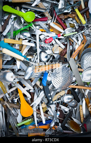 looking down into an assorted pile of mixed secondhand cutlery and cooking utensils in a huge box - Stock Photo