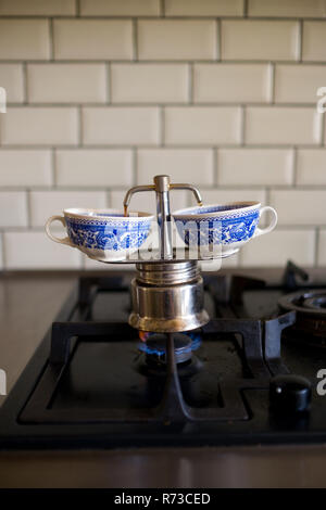 close up of an italian moka pot with twin spouts on a gas hob beginning to serve two expressos into two vintange china cups with blue flowery motifs - Stock Photo