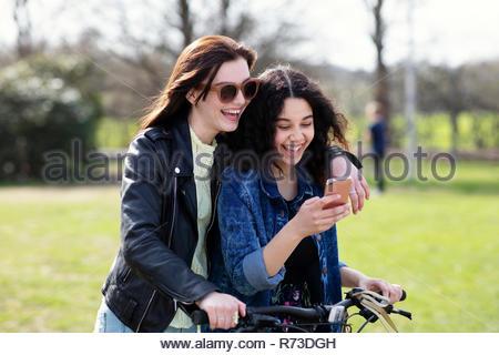 Teenage girls reading text together on push bike - Stock Photo