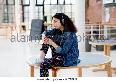Teenage girl using headphones in school - Stock Photo