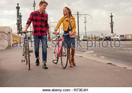 Couple walking bicycles across bridge, Budapest, Hungary - Stock Photo
