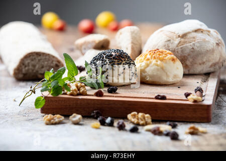 Seeded bread rolls and rustic loaves on chopping board, still life - Stock Photo