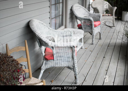 Wicker chairs on a gray porch. - Stock Photo