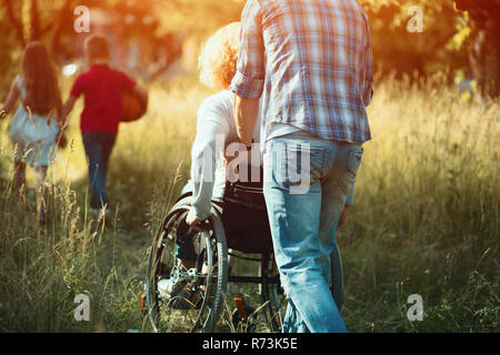 Man pushes woman in wheelchair to run after kids - Stock Photo