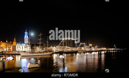 Overlooking the city front and the quay of the city of Kampen at the river IJssel.  Long Exposure photography with just lighted boats along the quay.  - Stock Photo
