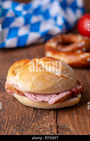 closeup of a bavarian leberkaese bun on dark wood - Stock Photo