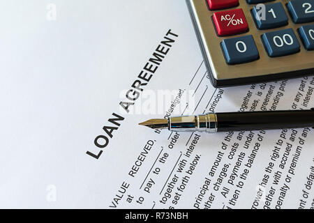 Business loan agreement or legal document concept. Fountain pen and calculator on loan agreement paper form. Loan agreement is a contract between a bo - Stock Photo