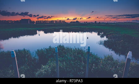 An old harbor head in the dry fallen polder of the Netherlands during sunset and the evening. A foot with contrasting and beautiful light - Stock Photo