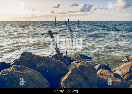 A lake at sunset with traditional fishing gear and waves that hit the coast - Stock Photo