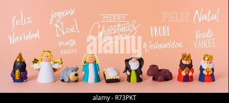 the holy family, an angel and the magi, and the text merry christmas in different languages, such as spanish, french, portuguese, czech or german, on  - Stock Photo