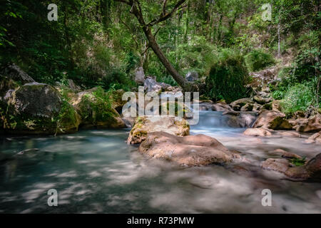 Photo from mountain river that runs usually in mountains, in narrow, deep valley with steep banks, rocky stream bed, and accumulated rock debris. Moun - Stock Photo
