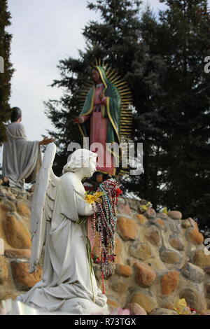 Our Lady of Guadalupe Shrine statue for Mexican immigrants and immigration and an angel covered in rosaries praying in des Plaines, Illinois, Nuestra Señora de Guadalupe, Virgin of Guadalupe - Stock Photo
