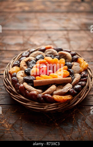 Mix of dried fruits in a small wicker basket on wooden table - Stock Photo
