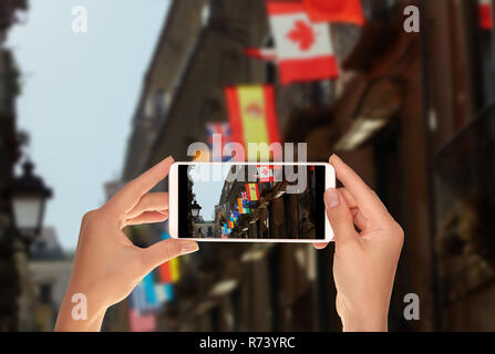 A tourist is taking a photo of flags of various world countries are hung out on one of the buildings in Italy on a mobile phone - Stock Photo