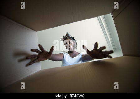 The surprised african woman unpacking, opening carton box and looking inside. The package, delivery, surprise, gift, lifestyle concept. Human emotions - Stock Photo
