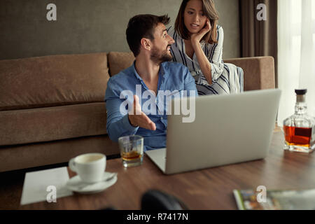 Couple enjoying time together browsing on laptop at home - Stock Photo