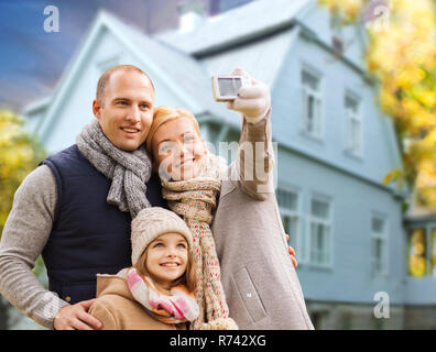 family takes autumn selfie by cellphone over house - Stock Photo