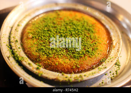 Traditional Turkish dessert 'Kunefe' in the restaurant table in Antakya, Turkey. - Stock Photo