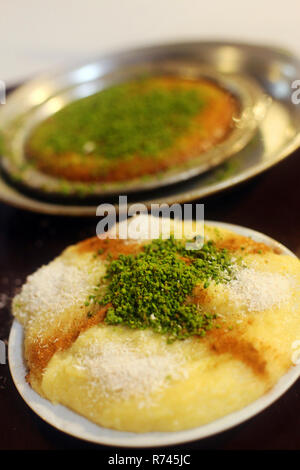 Traditional Turkish desserts 'Cheese Dessert' and 'Kunefe' in the restaurant table in Antakya, Turkey. - Stock Photo