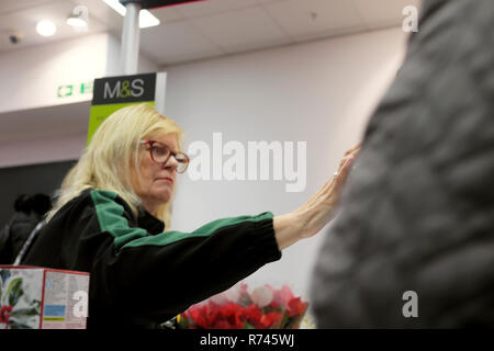 An older female worker working at a till on the checkout counter in M&S Marks and Spencer food grocery store in Great Britain UK. KATHY DEWITT - Stock Photo