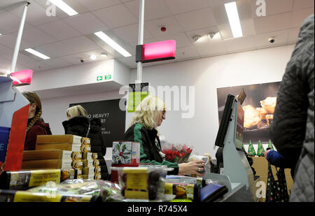 An older female worker working on the checkout counter in M&S Marks and Spencer food grocery store in Great Britain UK. KATHY DEWITT - Stock Photo
