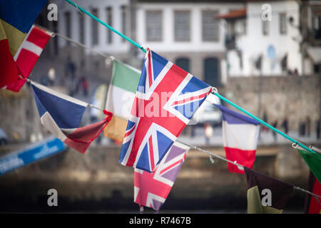 A flag of the United Kingdom waves amidst other national flags (Ireland, France, Denmark), against an old town background. - Stock Photo