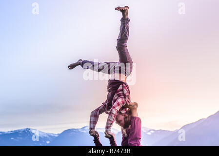 Two young women practicing acroyoga in front of mountain range at sunset, Squamish, British Columbia, Canada - Stock Photo