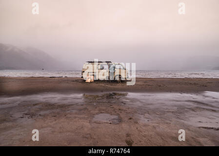 Woman and pet dogs by camper van on beach, Chile - Stock Photo