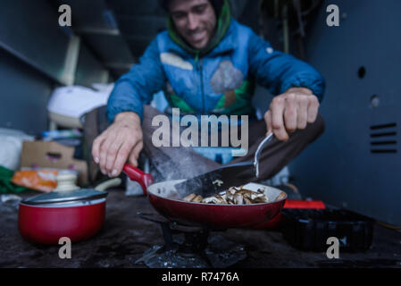 Young male rock climber cooking breakfast in camper van - Stock Photo