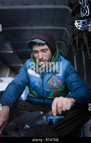 Young male rock climber preparing climbing equipment in camper van - Stock Photo