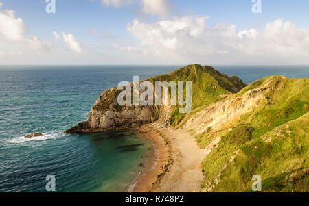 Morning sun shines on cliffs and beaches at Man O'War Bay near Durdle Door in Lulworth, Dorset, on England's Jurassic Coast World Heritage Site. - Stock Photo