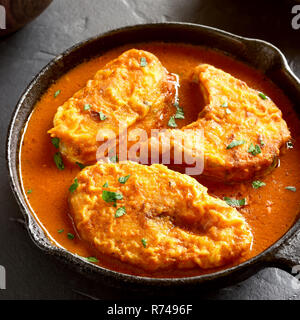 Close up of fish curry in frying pan on black stone table. Indian style food - Stock Photo