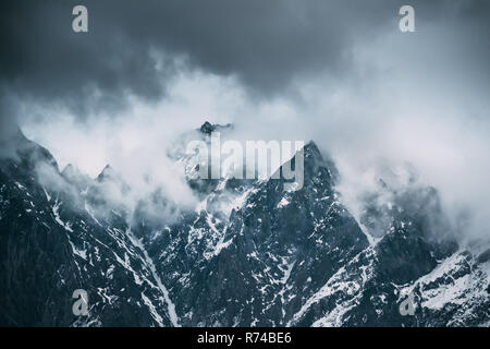 Clouds Fly Low Over Rocks. Mountains Peaks Covered With Snow. Varied Mountain Landscape In Mtskheta-Mtianeti Region, Georgia. - Stock Photo