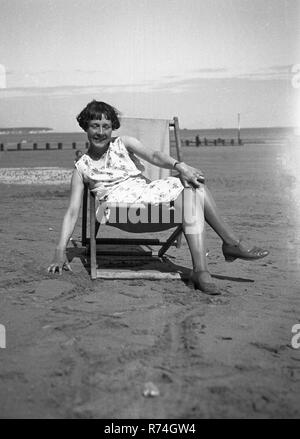1930s, historical, young woman in a deckchair on a sandy beach.