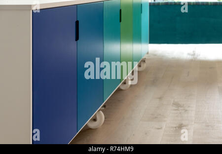 Movable kitchen island on industrial castor wheels, retro design, painted in blue and green ombre colours - Stock Photo