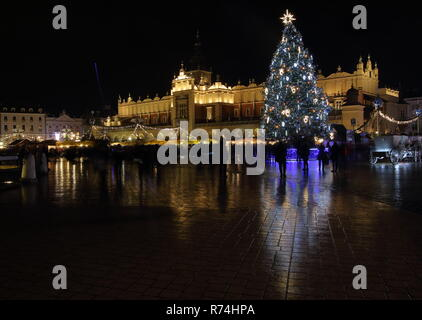Night cityscape of Krakow, Poland, city center with historical illuminated building, Christmas tree, decoartions, reflections on wet ground. - Stock Photo